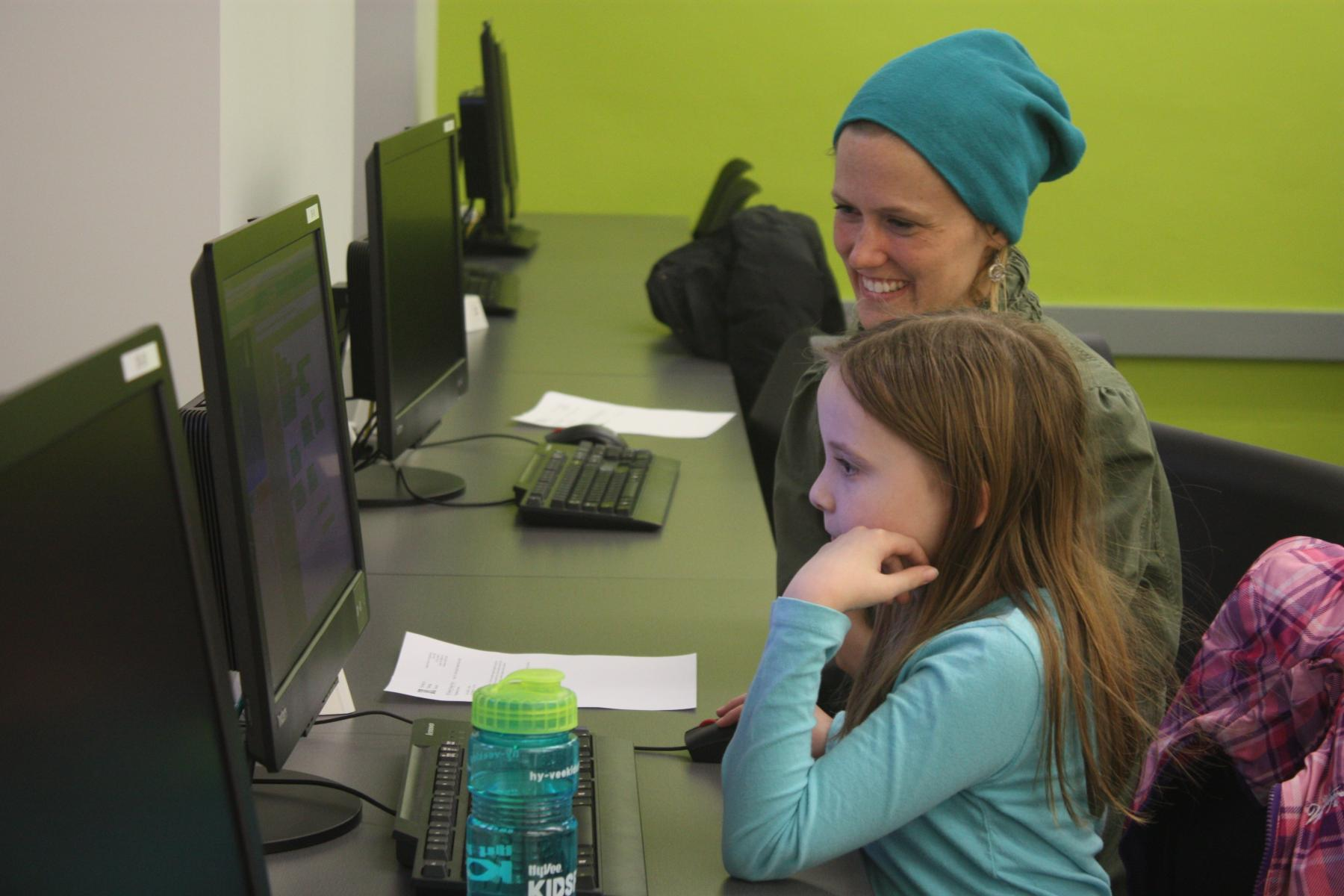 CADDY Gretchen Larsen assists a student with her coding project during the first CADDY workshop.