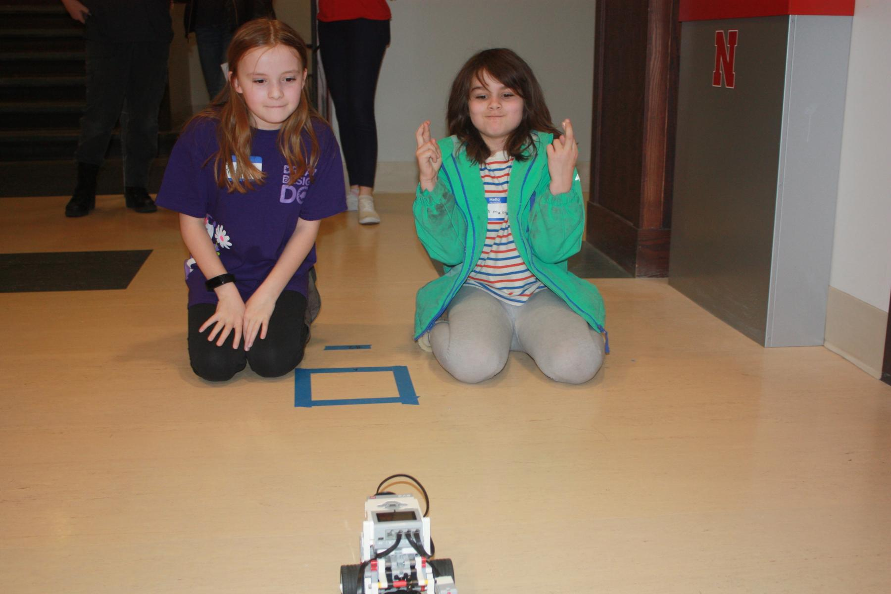 Two Girl Scouts anxiously await successful results in programming their robot.
