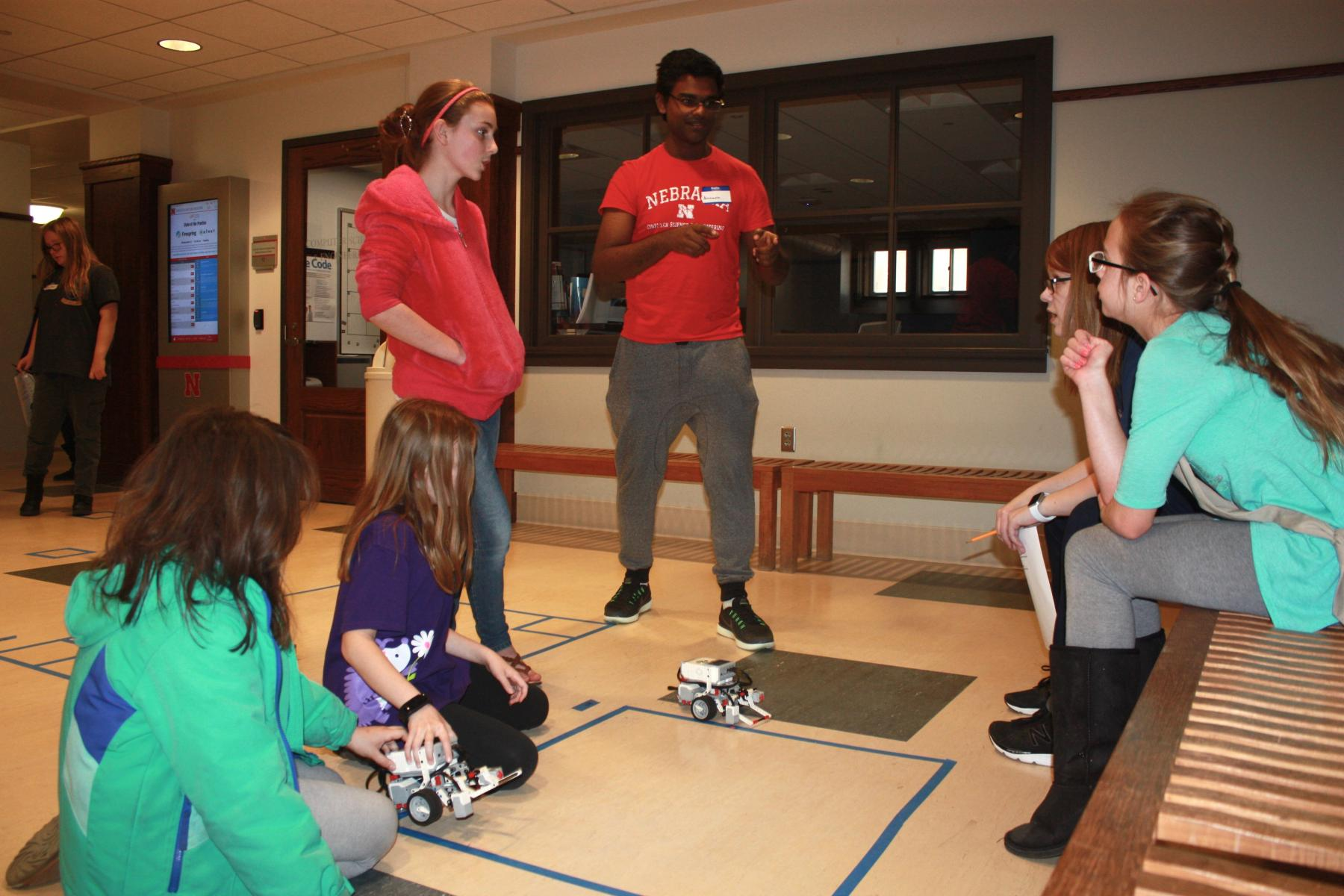 Girl Scouts and student mentors work together to program robots.