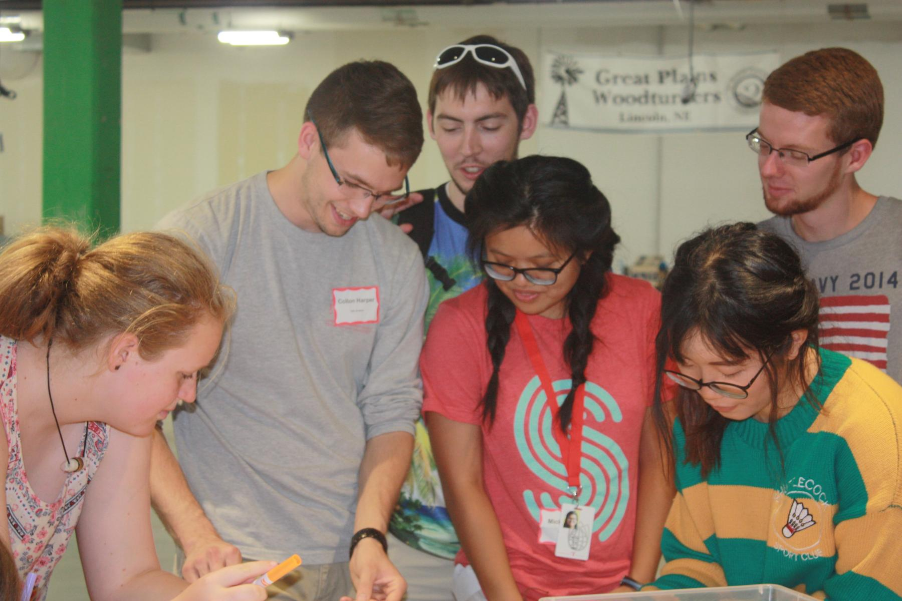 Student mentors and Girl Scout campers gather to work on a button project at Nebraska Innovation Studio.
