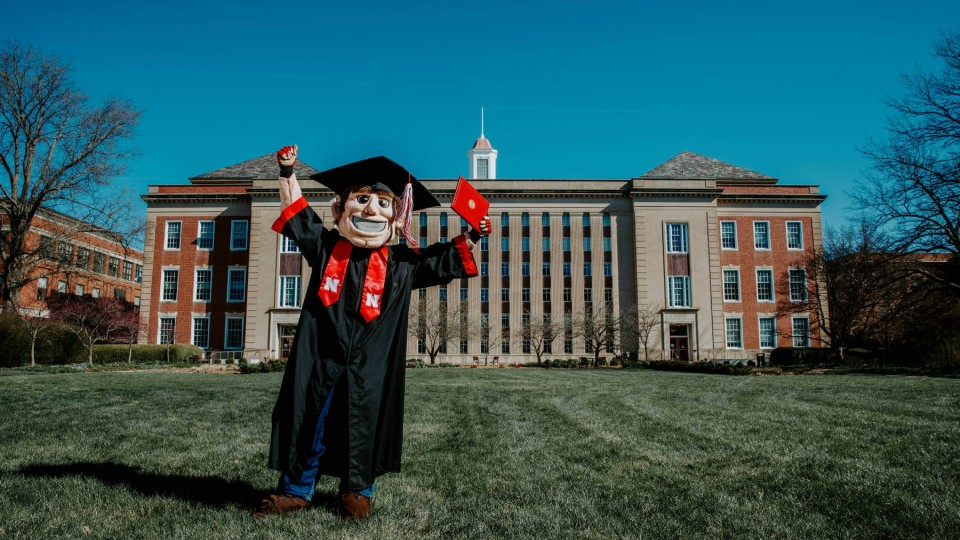 Mascot Herbie Husker holds a diploma.
