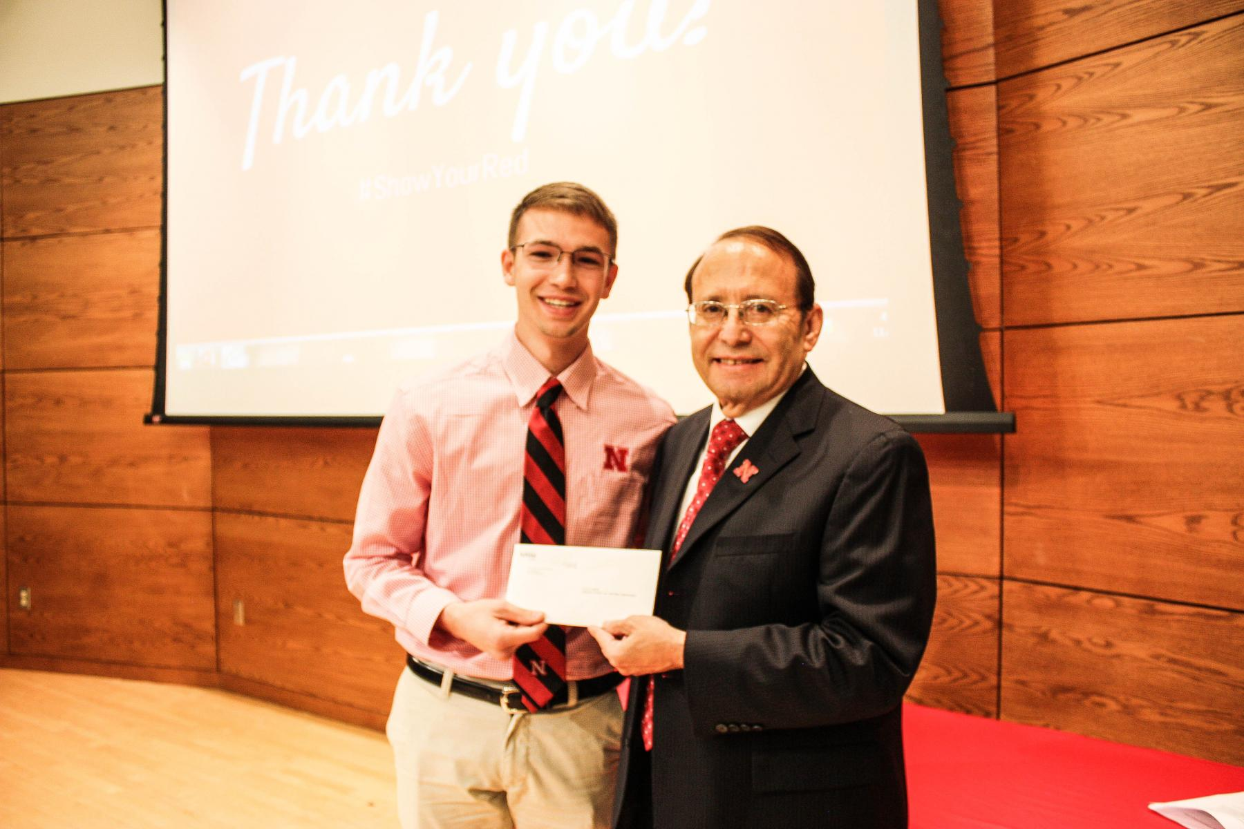 CSE Ambassadors president Colton Harper accepting the grant from Dr. Juan Franco.