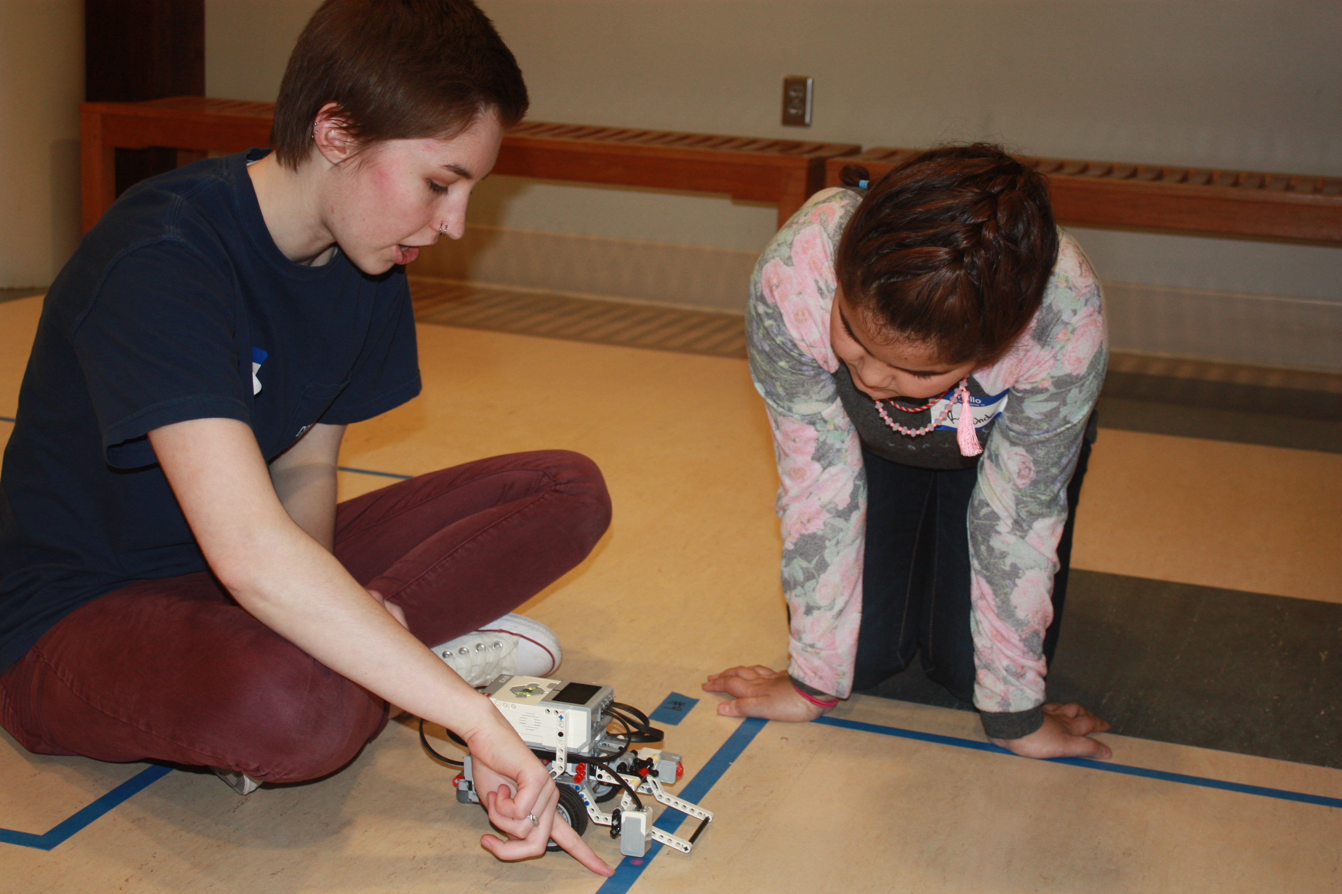 Computing for All member Allison Buckley helps a Girl Scout program a robot.