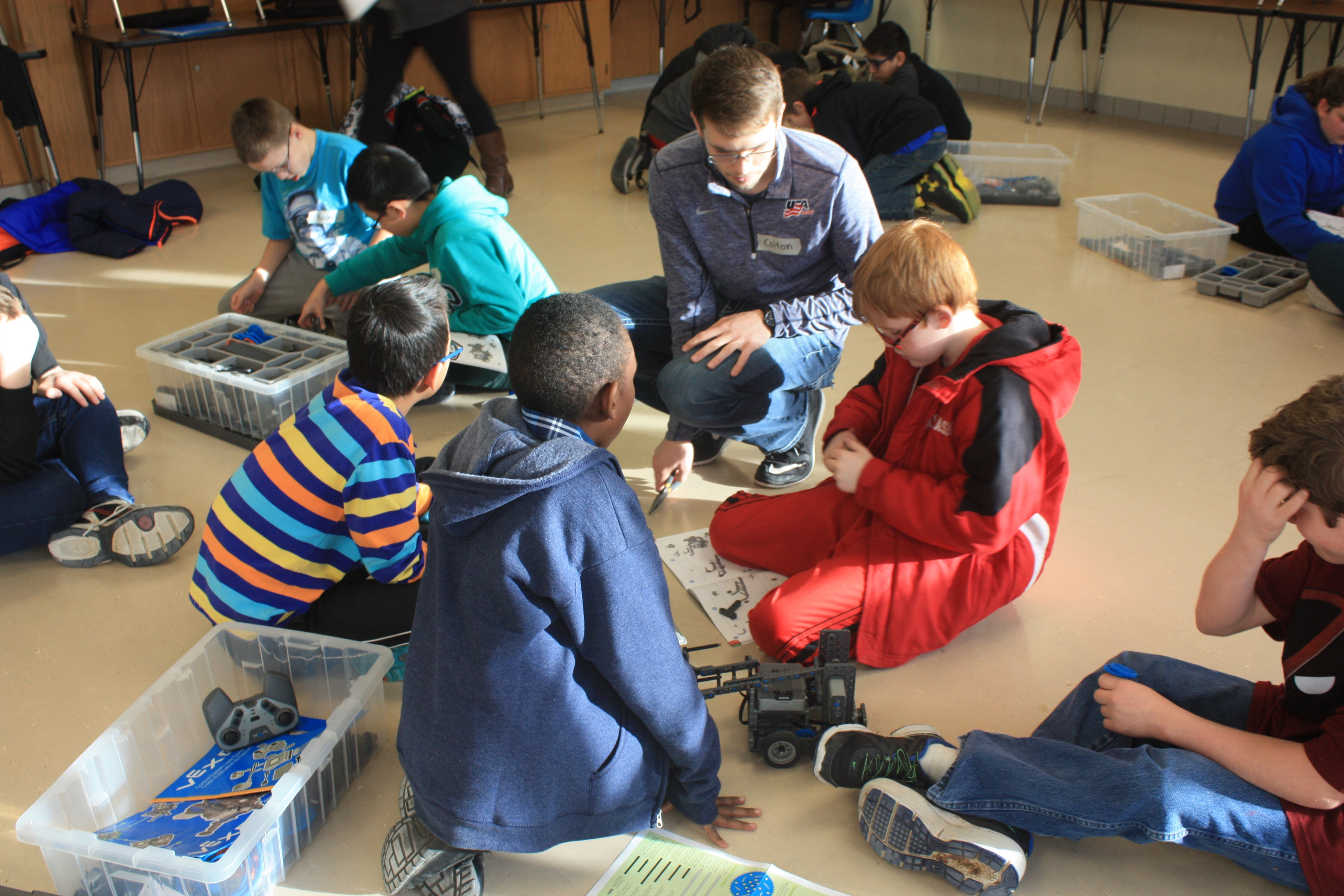 CSE Ambassador Colton Harper helps students at Culler Middle School put together robots in an after-school club.